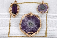 Gold wire-wrapped gems and fossils by Kristine Cooke